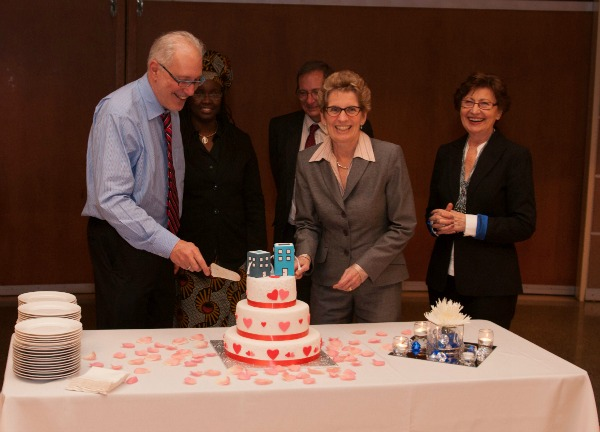 Premier of Ontario, Kathleen Wynne, cutting the wedding cake with Ryerson University President, Sheldon Levy, at the Social Planning Toronto symposium with a marriage/wedding theme. Photography by Jeremy Tudor Price