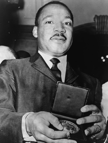 Martin Luther King, Jr. showing his medallion received from New York City Mayor Wagner, 1964
